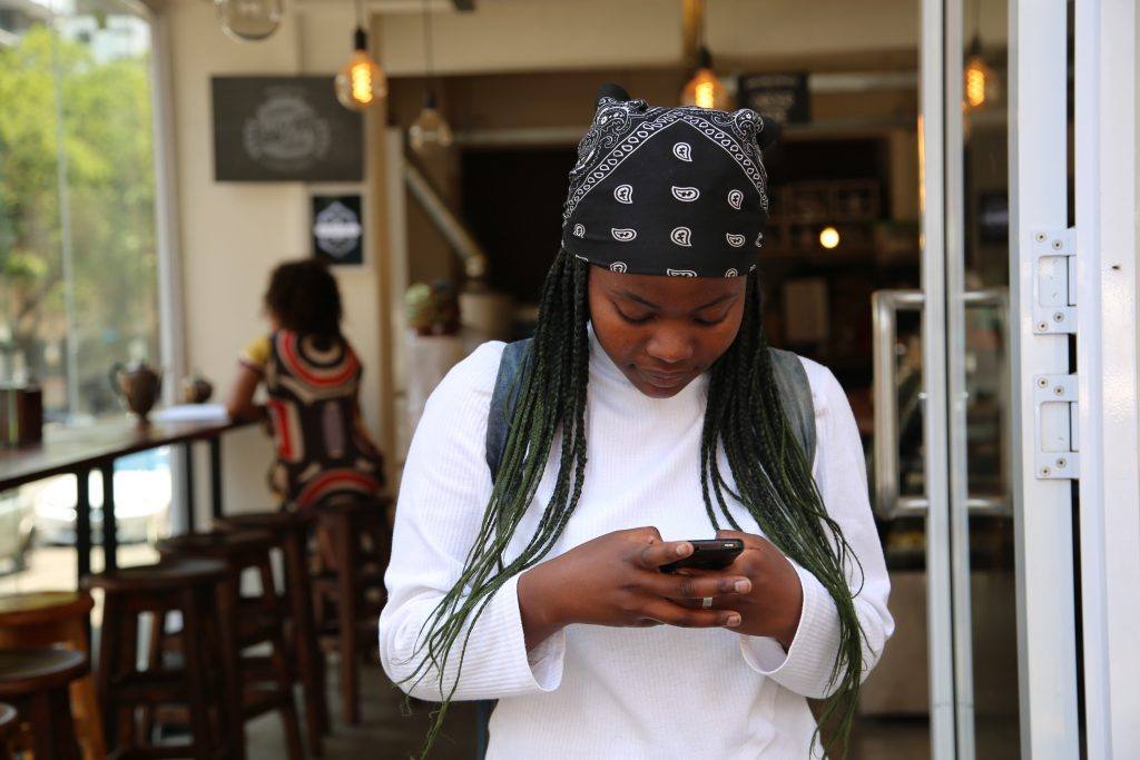 Woman standing in front of restaurant with her phone