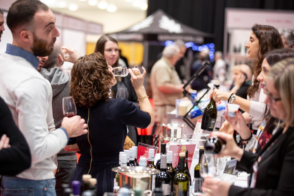 Trade show attendee tasting wine at a booth