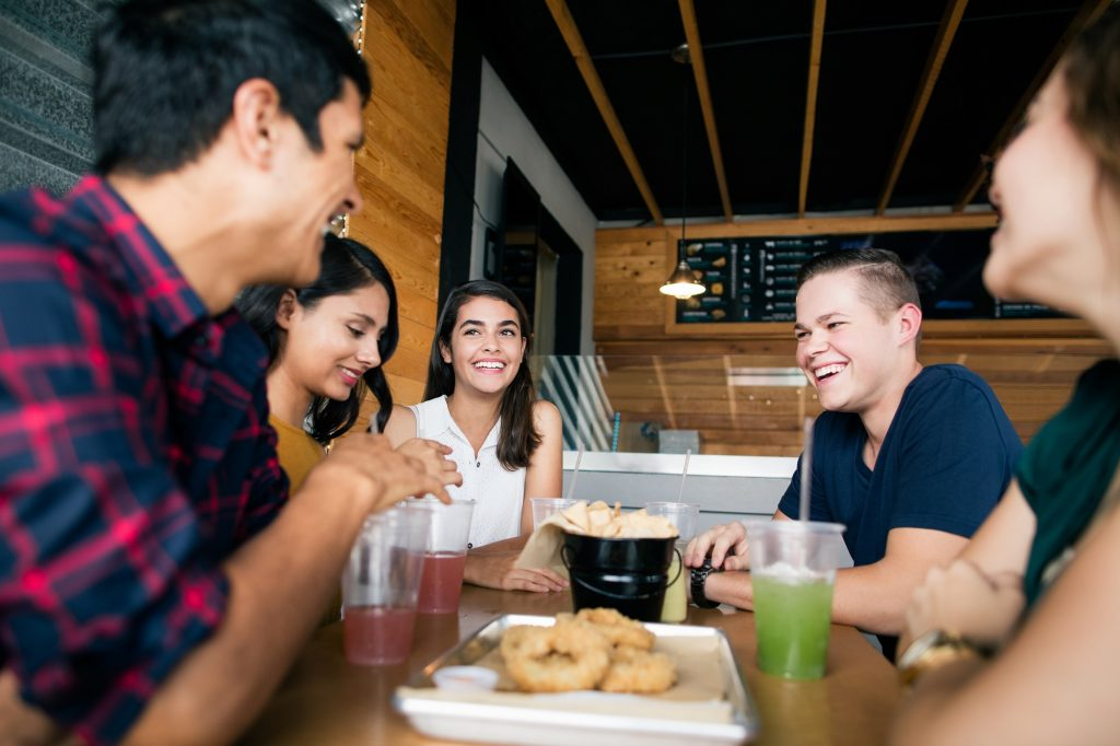 A small group of happy young people sitting in a restaurant, eating and smiling at each other.