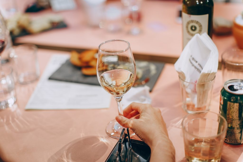 person holding wine glass on table at a restaurant
